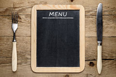 Blackboard menu, fork and knife. On old wooden background Royalty Free Stock Image