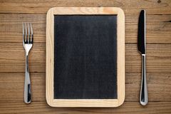 Blackboard for menu, fork and knife on table Royalty Free Stock Photography