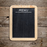 Blackboard menu. On old wooden background Stock Photography