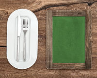 Blackboard for Menu or Recipe. Green chalkboard with white plate. Knife and fork on wooden table Stock Photography