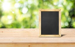 Blackboard menu on wooden table top food stand with blur garde. N green nature bokeh and leaf at foreground,Mock up for display or montage of product or design Stock Image