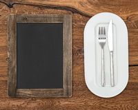 Blackboard for menu on wooden table. With white plate, knife and fork Stock Photo