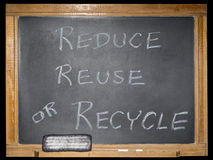 Blackboard message isolated background. The grungy scratched and worn blackboard displays a printed message in chalk.  The concept is reducing waste or recycling Royalty Free Stock Photos