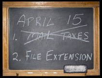 Blackboard message isolated background. The grungy scratched and worn blackboard displays a printed message in chalk.  The concept of tax deadline is decision Stock Images