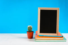 Blackboard with mock up frame and book pencil on the wood table Royalty Free Stock Image