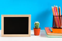 Blackboard with mock up frame and book pencil on the wood table Royalty Free Stock Images
