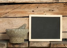 Blackboard and mortar on wooden background Stock Photography