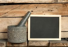 Blackboard and mortar on wooden background Royalty Free Stock Image
