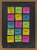 Blackboard with motivational reminders. Colorful crumpled sticky notes with uplifting and motivational words of wisdom posted on blackboard Royalty Free Stock Image