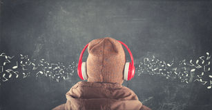 Blackboard with musical notes drawn. Teenager standing in front of a blackboard with musical notes drawn and listening to music on headphones Royalty Free Stock Images