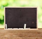 Blackboard na zielonej natury zamazanym tle fotografia royalty free