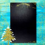 Blackboard Nativity menu. Gold Christmas tree and empty blackboard on blue wooden table Stock Image