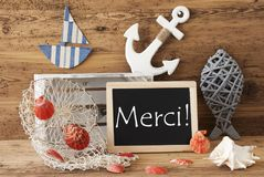 Chalkboard With Summer Decoration, Merci Means Thank You. Blackboard With Nautical Summer Decoration And Wooden Background. French Text Merci Means Thank You Royalty Free Stock Photos