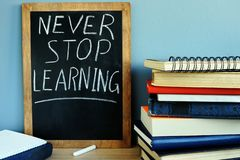 Blackboard with Never stop learning and books. stock photography