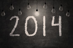Blackboard with New year 2014. New year 2014 text with light bulb on blackboard Royalty Free Stock Image