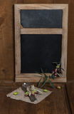 Blackboard with olives and tableware Stock Images