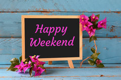 Blackboard over blue wooden shelf with the phrase happy weekend Royalty Free Stock Images