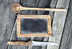 Blackboard over vintage wooden background Royalty Free Stock Photo