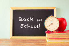 Blackboard with the phrase back to school, apple clock and stack of books. filtered image Royalty Free Stock Image