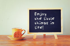 Blackboard with the phrase enjoy the little things in life next to coffee cup over wooden table.  Royalty Free Stock Photos