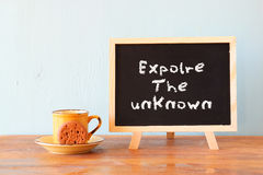 Blackboard with the phrase explore the unknown next to cup of coffee and cookie.  Royalty Free Stock Image