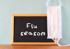 Blackboard with the phrase flu season written on it and face mask. Royalty Free Stock Images
