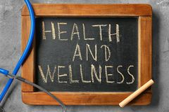 Blackboard with phrase \'Health and wellness\' and stethoscope on grey background stock image