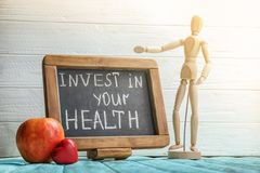 Blackboard with phrase Invest in your health on wooden table royalty free stock images