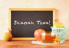 Blackboard with the phrase shana tova, apple, honey and pomegranate symbols of rosh hashanah holiday.  Stock Photos