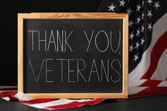 Blackboard with phrase Thank You, Veterans and American flag on grey table. Memorial Day