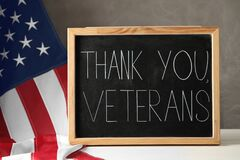 Blackboard with phrase Thank You, Veterans and American flag on white wooden table. Memorial Day
