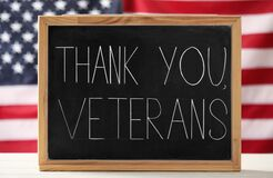 Blackboard with phrase Thank You, Veterans on white wooden table against American flag. Memorial Day