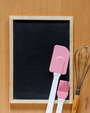 Blackboard with pink silicone spatula and hand whisk mixer. Royalty Free Stock Photography