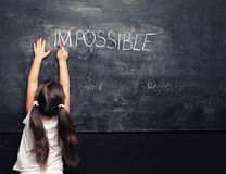 Blackboard possible. Cute little girl putting a cross over impossible on blackboard Stock Photography