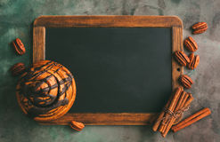 Blackboard for recipes or food menu. Cinnamon rolls, cinnamon sticks and pecans. Toned image Stock Images