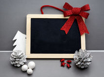 Blackboard with red ribbon and pine cones Royalty Free Stock Image