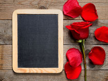 Blackboard and red rose Stock Images