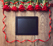 Blackboard and red roses on wooden background Stock Image