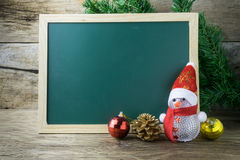 Blackboard With Red Santa Hat And Christmas snowman toy on old w Royalty Free Stock Photos