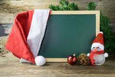 Blackboard With Red Santa Hat And Christmas snowman toy Stock Photos