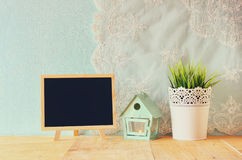 Blackboard with room for text, vintage Flower pot and lantern as a bird house against mint wall and antique lace fabric Royalty Free Stock Images