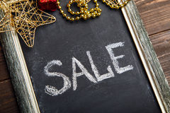 Blackboard with Sale text and New Year decorations Stock Photos