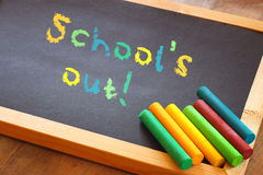 Blackboard with schools out text written in colorful letters Stock Photos