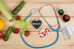 Blackboard in shape of heart with text Obesity, stethoscope and choice between natural vitamins, vegetables, fruits and berries or. Tablets and pills on wooden royalty free stock photos