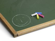 Blackboard with smiley and crayons Royalty Free Stock Images