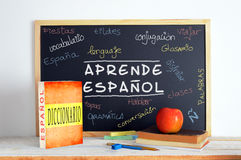Blackboard in an Spanish language class. Blackboard in a Spanish class. Some books and school stuff for studying Spanish language in a classroom Royalty Free Stock Images