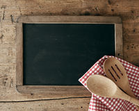 Blackboard and spoons. Blackboard on wooden surface and serving spoons stock photo