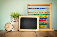 Blackboard, stack of colorful beaded abacus and clock. back to school concept Stock Image