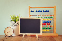 Blackboard, stack of colorful beaded abacus and clock. back to school concept Royalty Free Stock Images