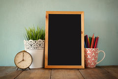 Blackboard, stack of colorful pencils and clock. back to school concept Royalty Free Stock Image